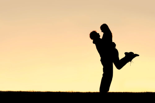 A silhouette of a happy young couple hugging, with the man lifting the woman off of her feet, at sunset.  Sky leaves room for copy-space.